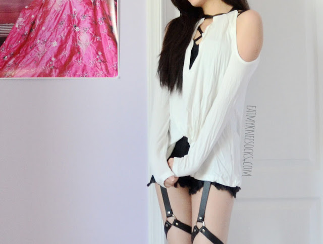 An edgy, grunge-style outfit with the leather-trim cold shoulder SheIn top, a strappy bralette, Harajuku-style frayed harness shorts, and spiked high-heel booties.