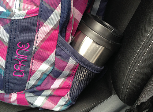 Backpack with travel mug of iced tea to go