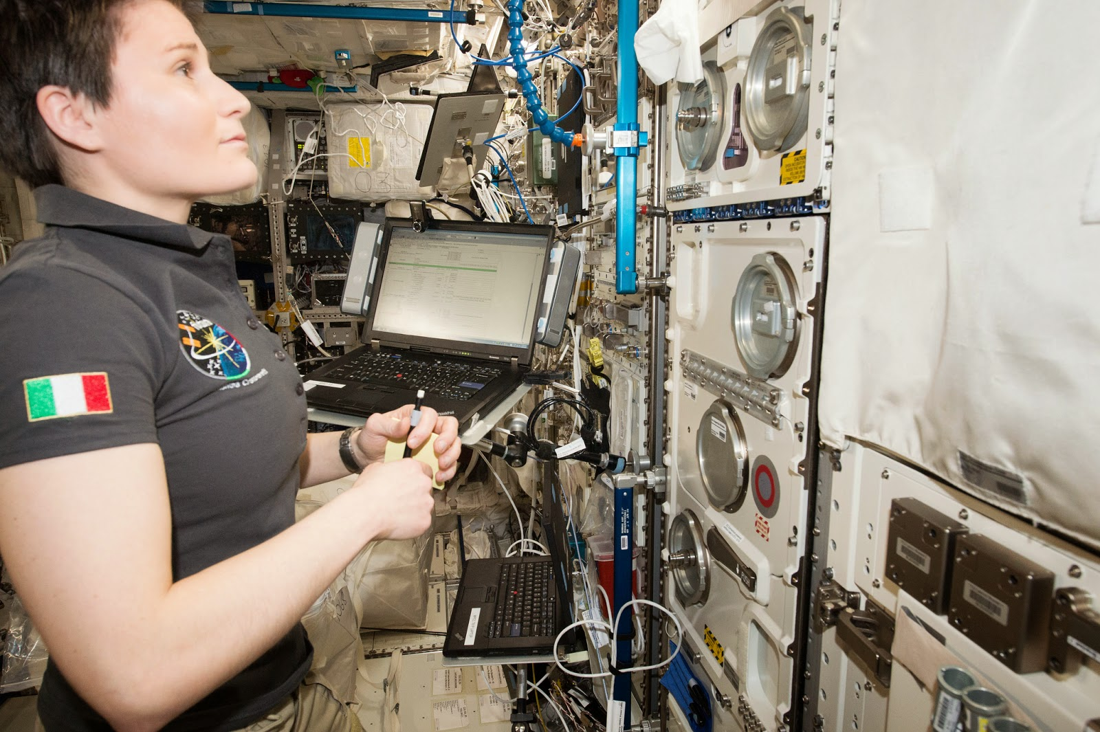 Samantha Cristoforetti, first Italian woman in space, Expedition 43 flight engineer aboard the International Space Station, is seen working on a science experiment that includes photographic documentation of Cellular Responses to Single and Combined Space Flight Conditions. Credit: NASA