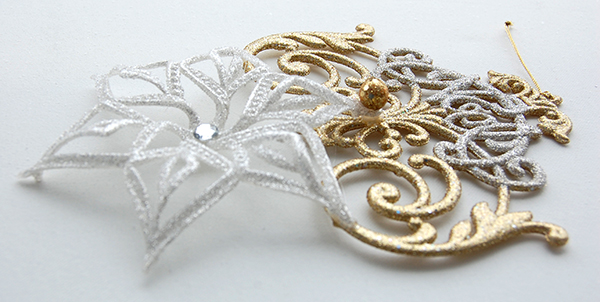White and gold noel ornament with white snowflack ornament upclose