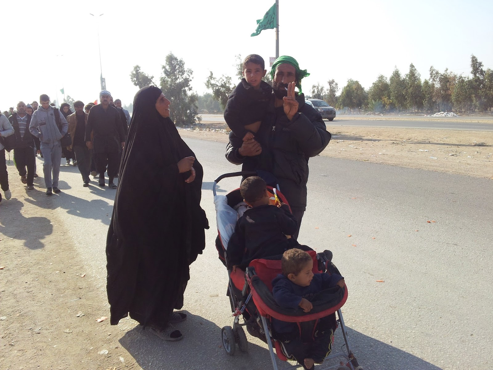 A man with three children walking towards Karbala in Arbaeen 2014