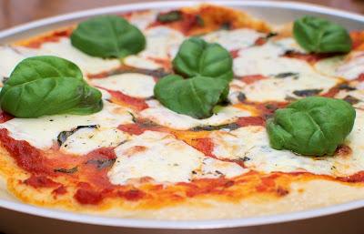 Una pizza Margarita que lleva tomate, mozzarella y varias hojas de albahaca