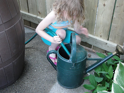 child operating a rain barrel