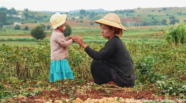 Bambina con la mamma in un campo in Myanmar
