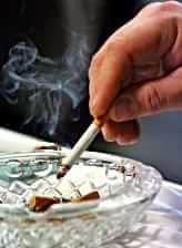 Mano che spegna una sigaretta nel portacenere