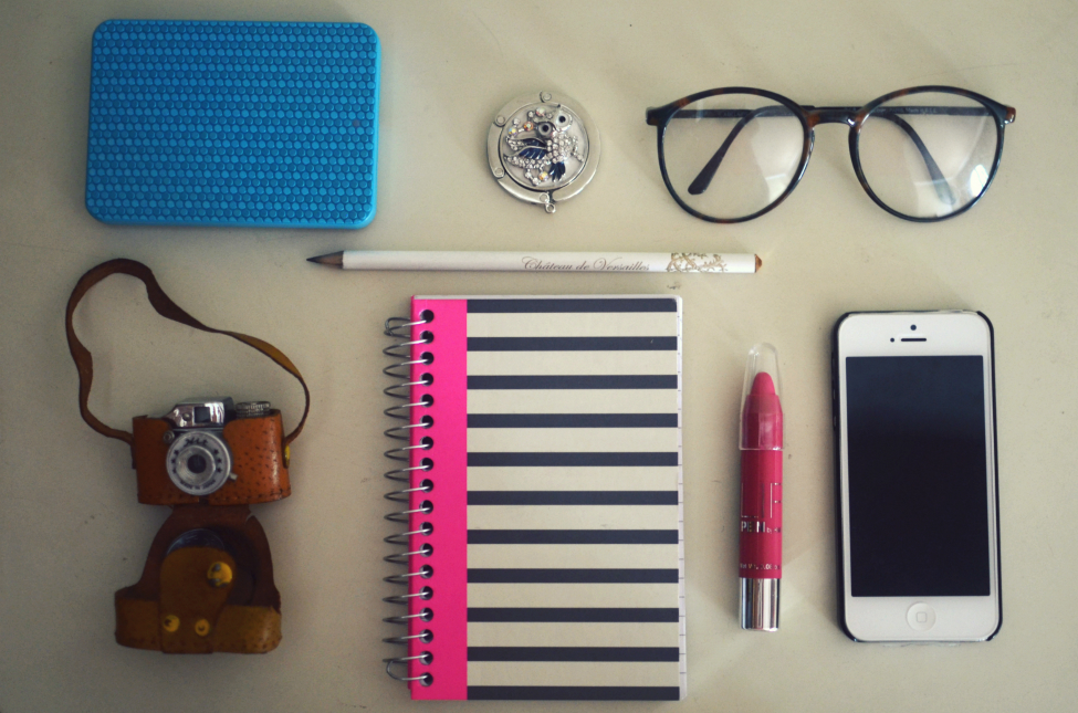 random objects: samsung hard drive, vintage mini camera, vintage eye glasses, notebok, pencil, iphone 5, lip pencil in fuschia, bag holder