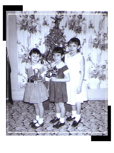 Sisters with dolls in front of Christmas tree.