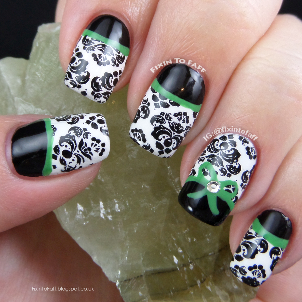 Signature style nail art black and white damask with black half moons and bright green detail, topped with a bow and a crystal.