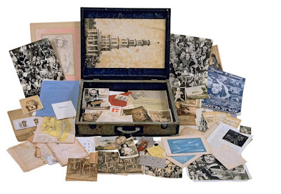 travel box containing and surrounded by assortments of letters, photos and magazines