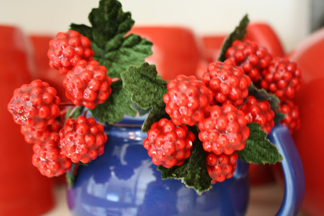 red berries in blue jug
