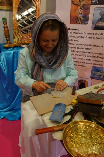 a woman hand carves a tiny stone