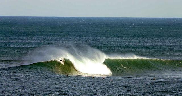 surfista cogiendo una ola en menakoz