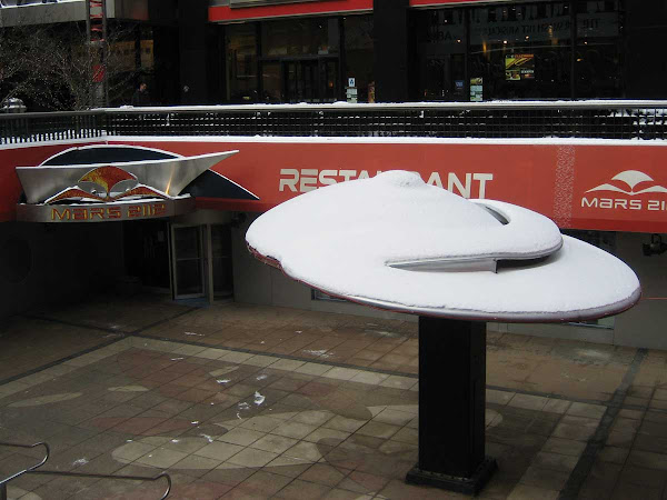 Flying Food - Snow turns Mars 2112's flying saucer into a cinnamon roll; at 51st St. & Broadway.