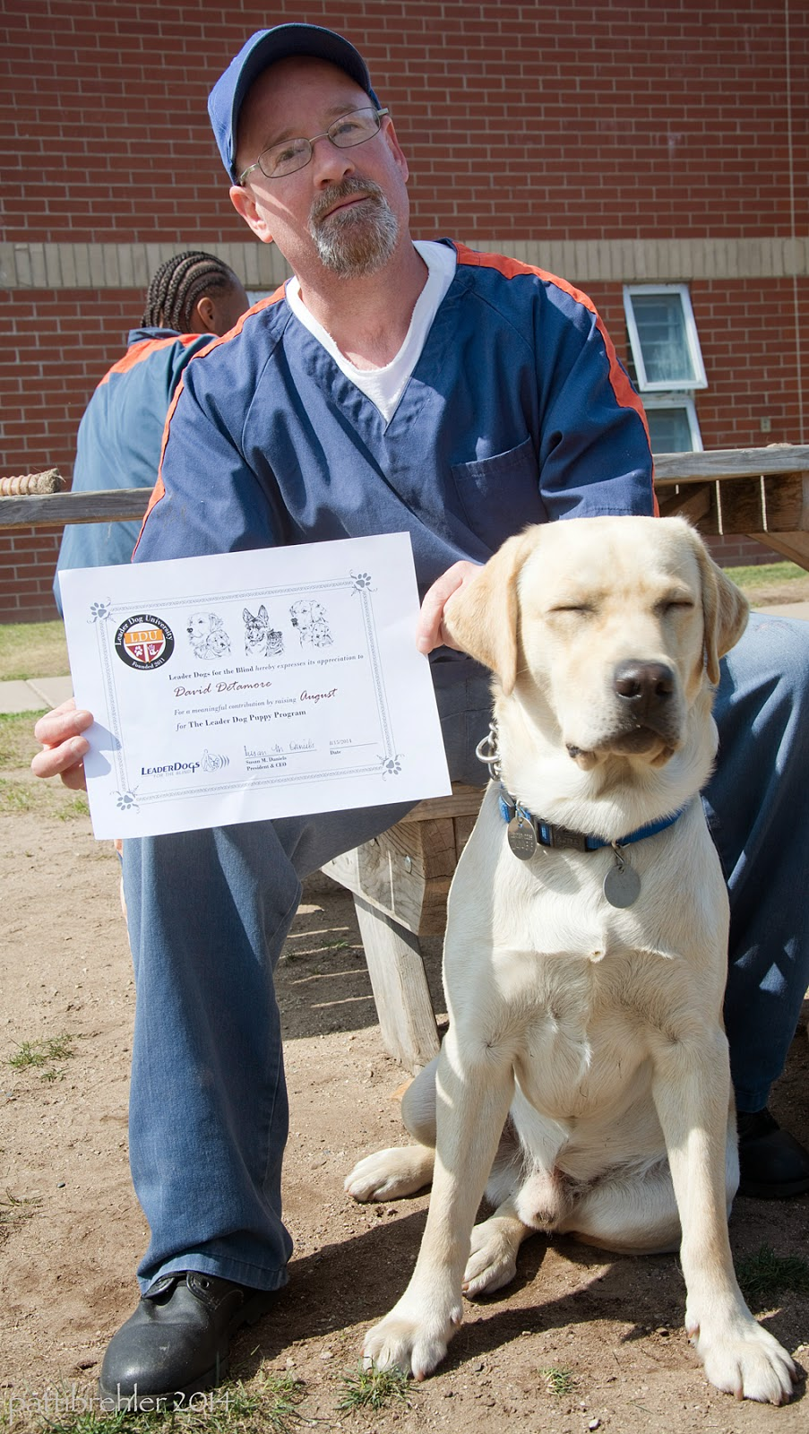 A man wearing glasses and the blue prison uniform with a blue ball cap is sitting in the sun on a picnic bench. He is holding a certificate in his right hand by his knee. A young yellow lab is sitting between his legs facing the camera. The dog's eyes are closed. There is a brick building behind them.