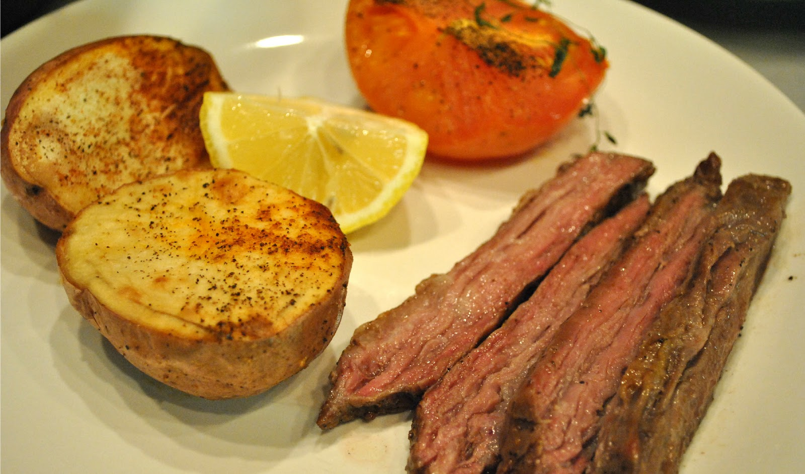 Skirt steak with lemon, chili-roasted potatoes, and roasted tomatoes