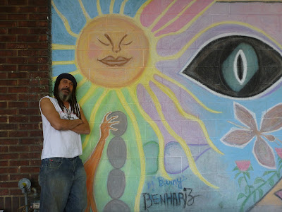 Artist Benny Benhariz Poses in Front of his Mural