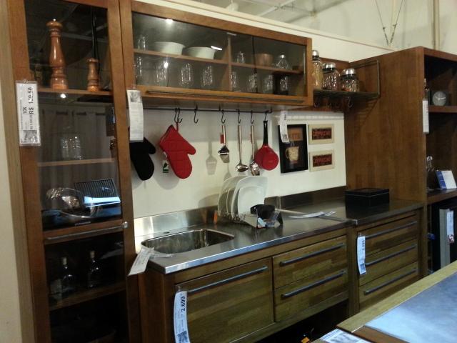 Pia de inox, gabinete em madeira e puxadores em ferro.