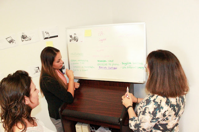Three women standing around a whiteboard