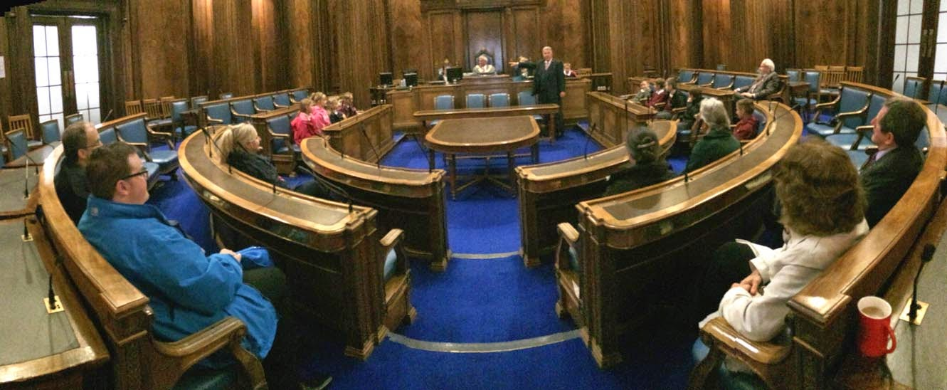 Panoramic picture of the wooden panelled, blue carpeted council chamber at Barnsley Town Hall.