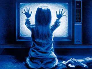 Famous image of Poltergeist's child sitting in front of the TV