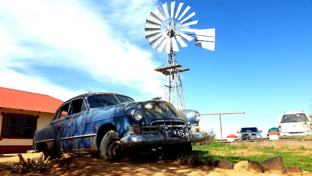 Old fashioned car next to a windmill at Canyon Road House Namibia