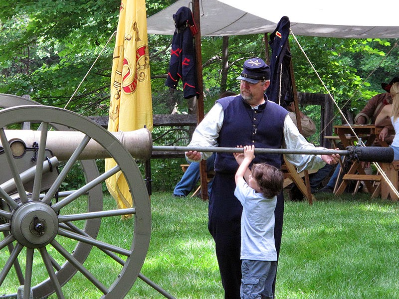 Civil War Invades Morristown - a young boy helps a reenactor load a cannon