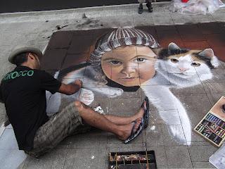 Streetart Festival Wilhelmshaven 2012 Mann zeichnet auf der Straße ein Kind mit einer Katze auf dem Rücken. Kind mit Mütze.