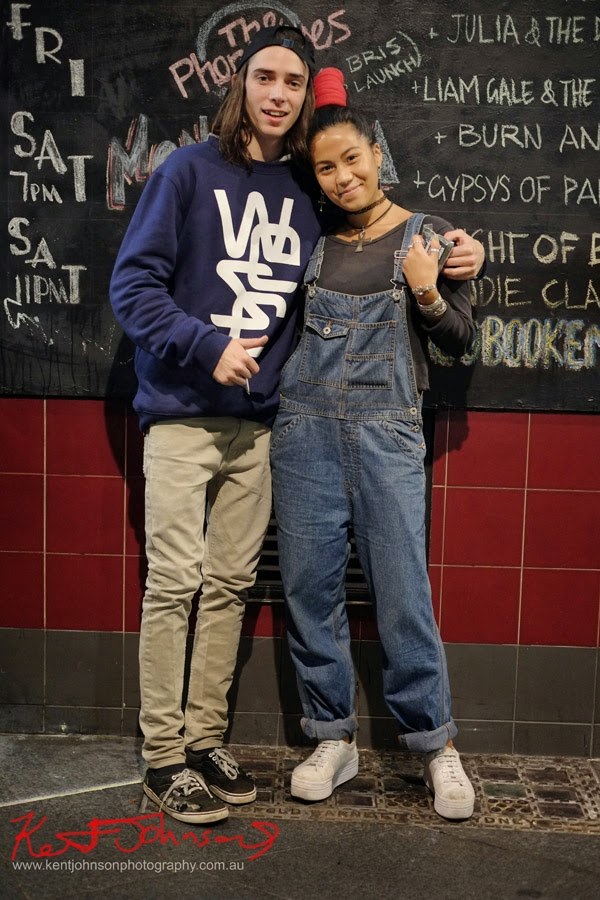Red topknot hair band, black long sleeve Tee and denim overalls with rolled cuff for her; backwards cap, light coloured skinny jeans and oversize Navy Sloppy Joe for him.