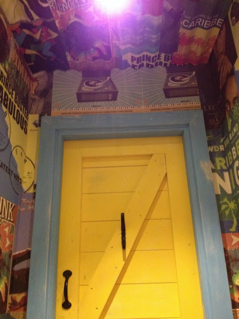 bright yellow door and fantastic wallpaper of posters of Bob Marley