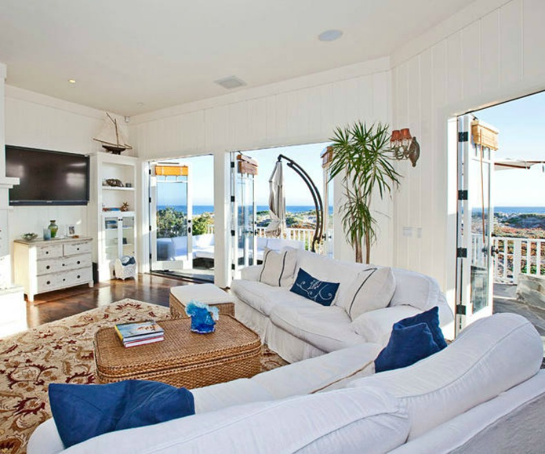 Coastal living room in blues and whites with slipcover sofa and ocean view