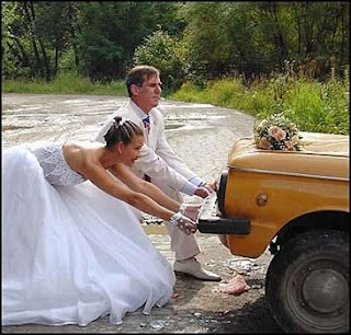 funny wedding picture: bride & groom dragging the car
