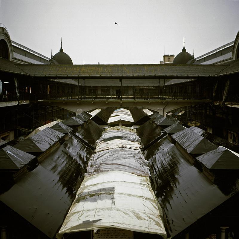 Vista de cima, a partir do 2º piso, sobre os toldos que abrigam as bancas do 1º piso. Foto em dia de chuva com muitos reflexos nas coberturas. Tons acinzentados e céu claro com uma pomba a voar