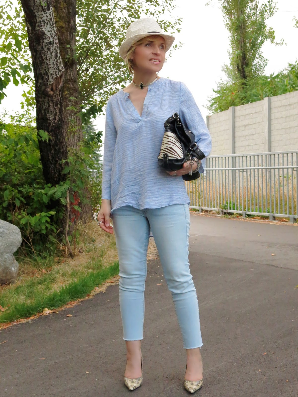 styling light-wash skinny jeans with a tunic, snake-print pumps, and a fedora
