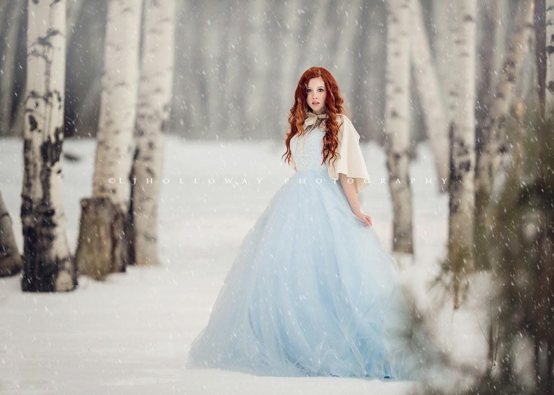 photo de Lisa Holloway représentant une jeune femme en robe blanche dans une forêt enneigée