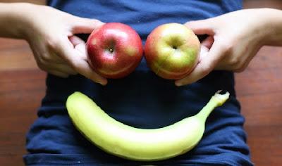 Cara con manzanas y plátano