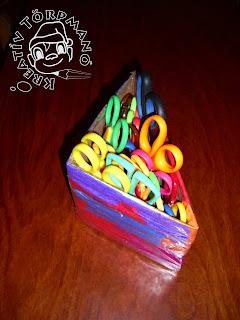 Szöveg: Praktikus, újrahasznált ollótartó. Kép: háromszög alakúra meghajlított karton, amire színes krepp-papír szalagocskák vannak ráaplikálva, bennük fogantyújukkal felfelé állított színes ollók.
