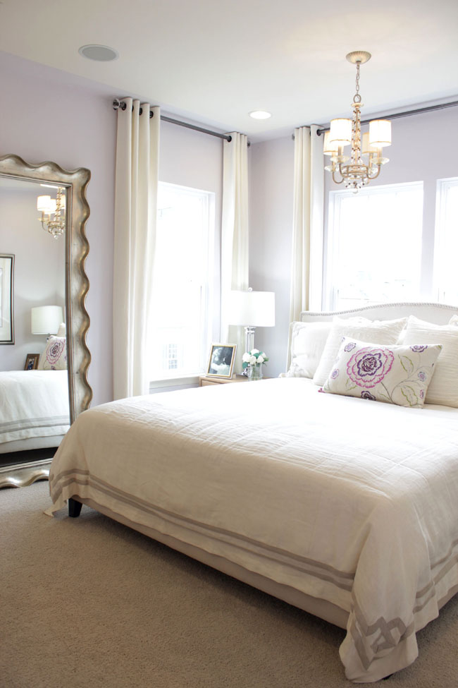 Bright bedroom with soft purple accents and big mirror on the floor