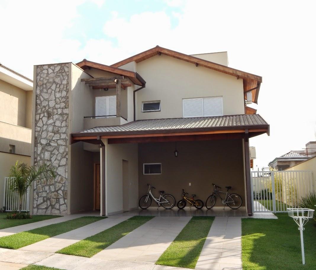 Um pergolado confere charme ao terraço sobre o alpendre da residência. A mescla de madeira e pedra na fachada confere maior acolhimento à residência.
