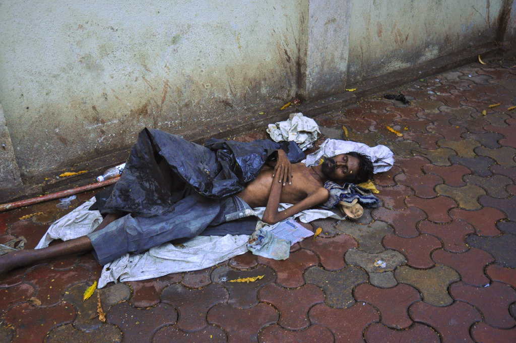 India photo of a man sleeping on the pavement