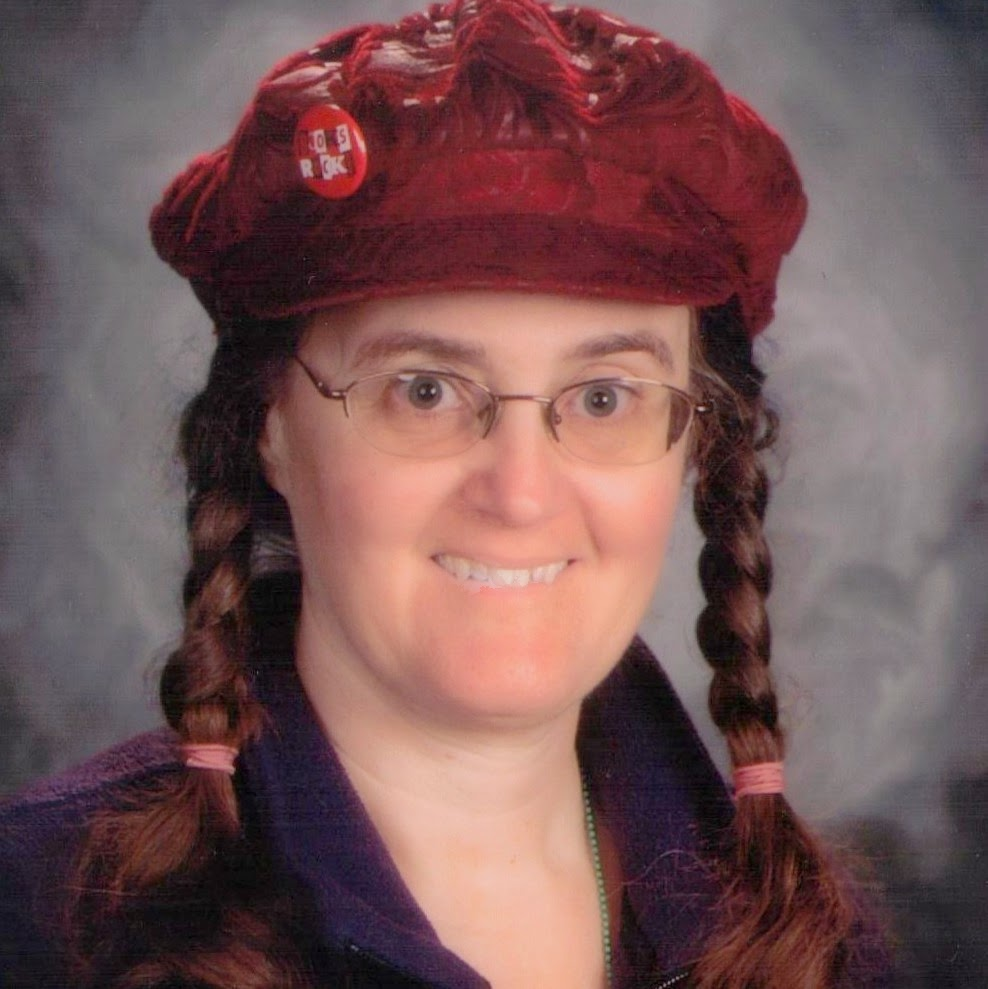 Close-up head and shoulders photo of Cynthia M. Parkhill wearing eight-paneled, dark red hat with brin and button that says, 'Books Rock.'