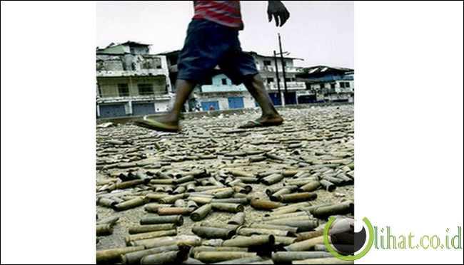 Foto kaki seorang bocah yang berjalan di atas hamburan peluru-peluru sisa perang