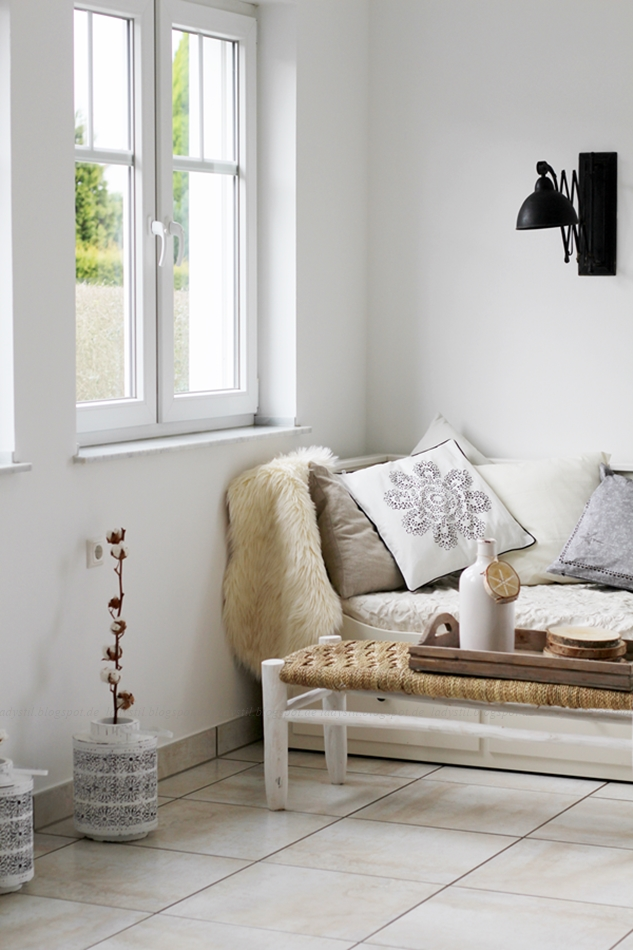 Tagesbett in der Küche mit weiß beigen Kissen und einer Sitzbank mit Geflecht schwarze Scherenlampe
