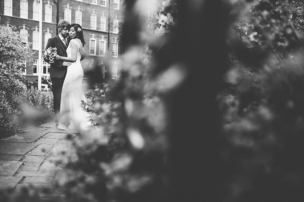 black and white photograph of wedded couple through the trees in mayfair park
