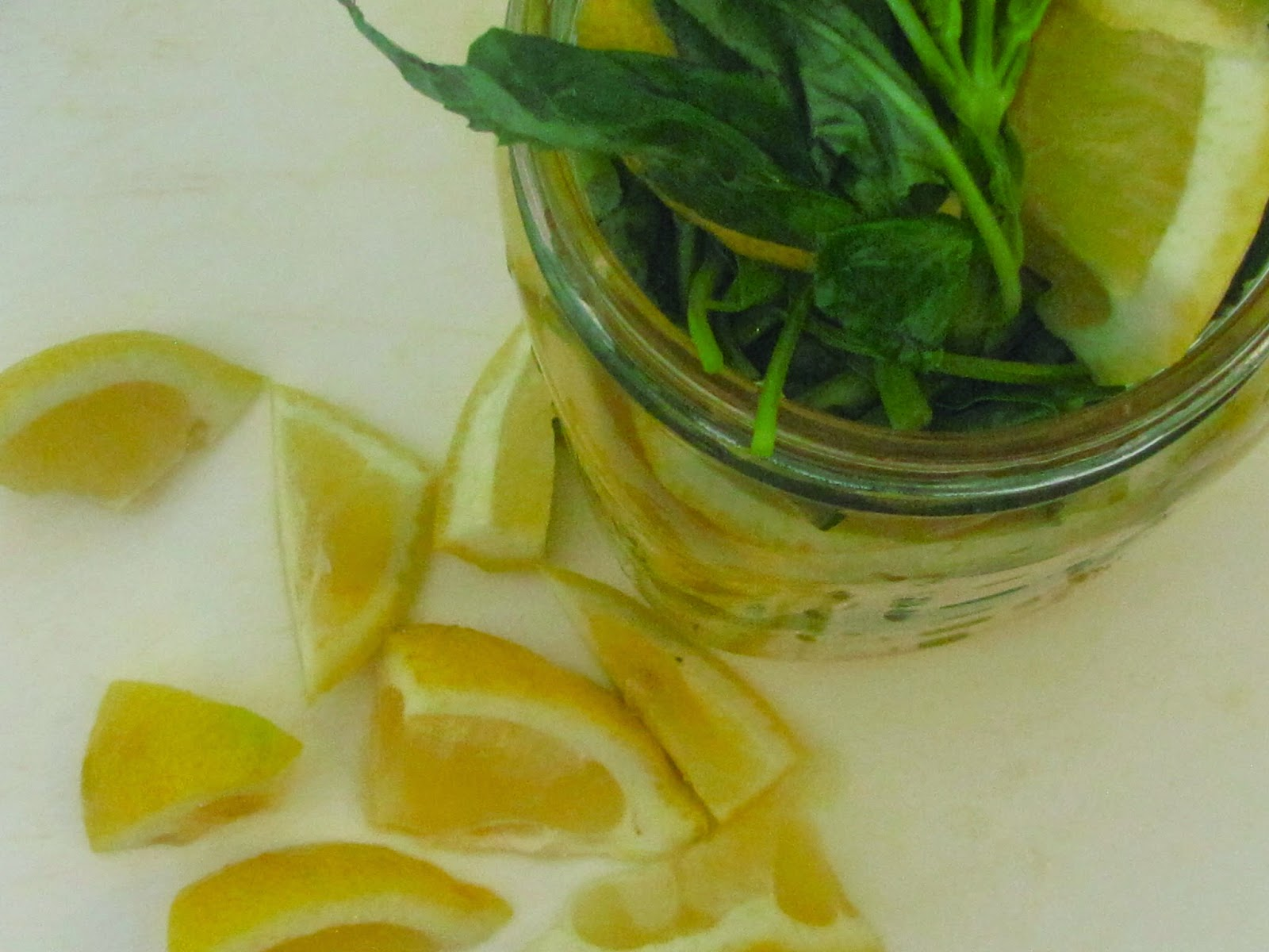 Chopped whole lemon and basil in a jar with simple syrup on a white chopping board