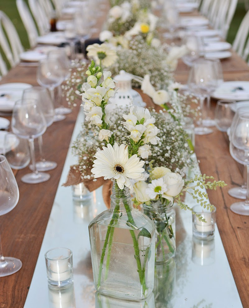 dinner centerpieces with mirror runner and varied jars and bottles