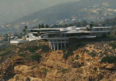 amazing house perched on the edge of a cliff with endless windows that look out on the ocean and other beautiful things curved walls big fireplace - Iron Man House