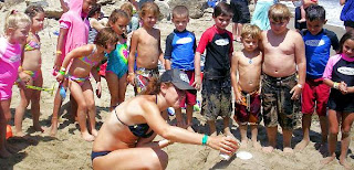 Campers watch the camp counselor build an erupting volcano on the sand at Keiki Camp.