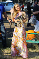 Joanna Krupa holding her dog and waving to cameras
