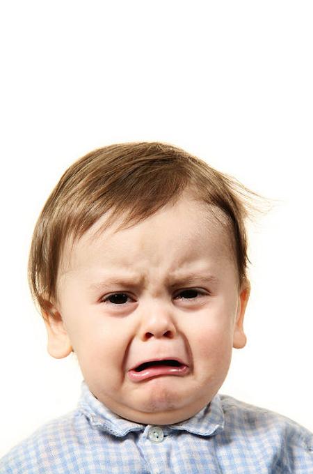 طفل بشعر جميل يبكي بعمق بصورة خلفية بيضاء
