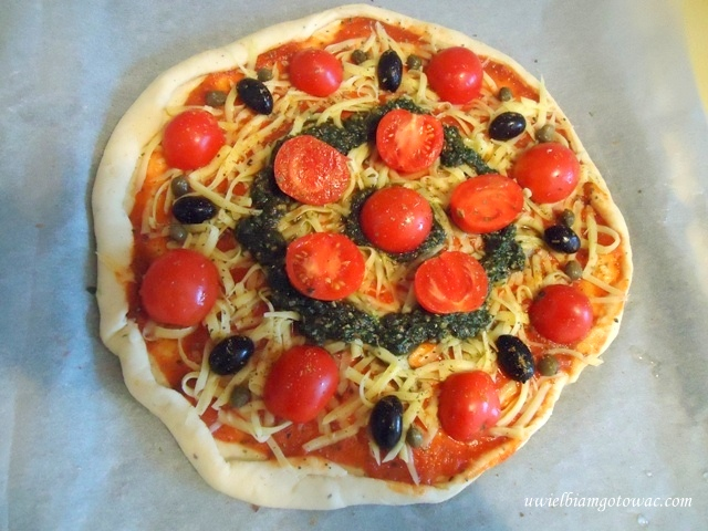 Pizza z pomidorkami koktajlowymi, pesto, kaparami i oliwkami